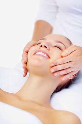 Smiling young woman enjoying a massage while at a dayspa